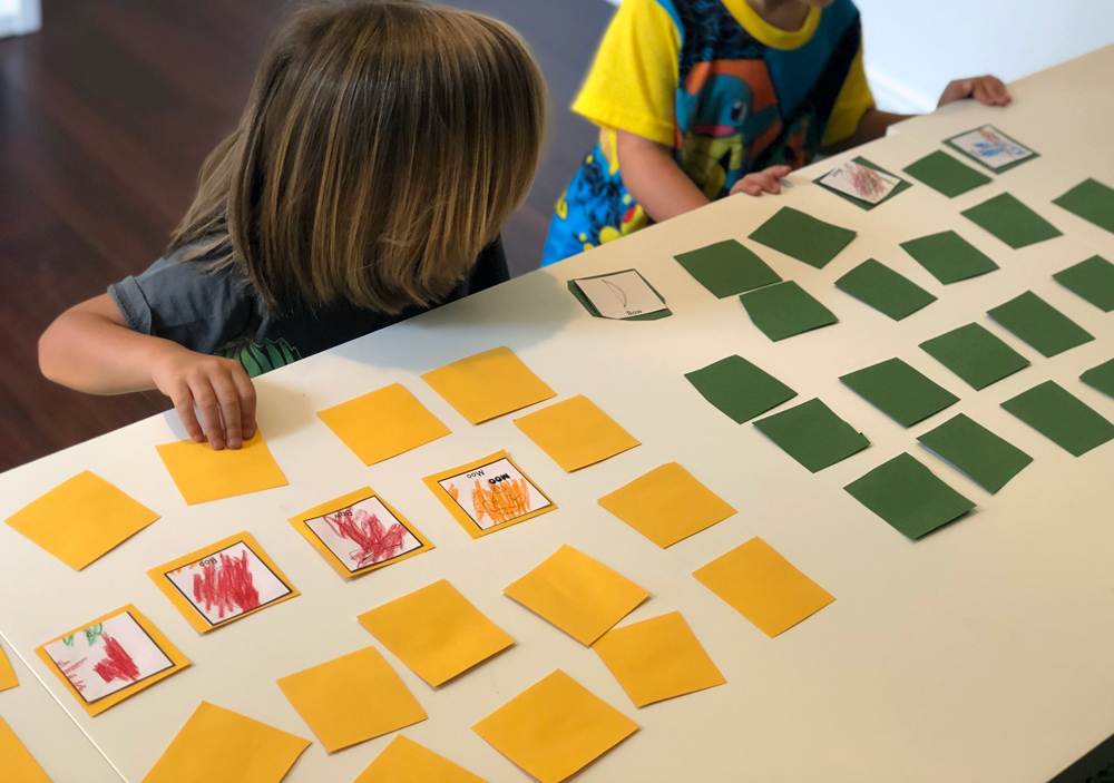 Kids playing a speech therapy game with post-its.