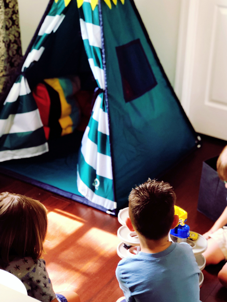 Kids gathered around a play tent.