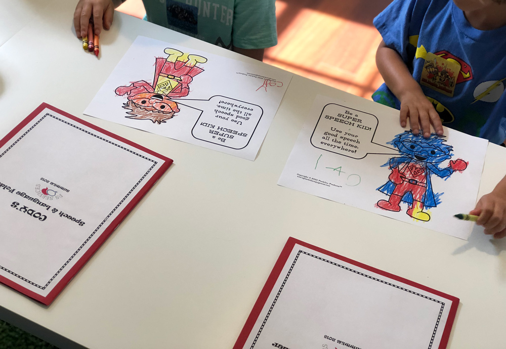 Two kids drawing and doing a speech therapy activity.