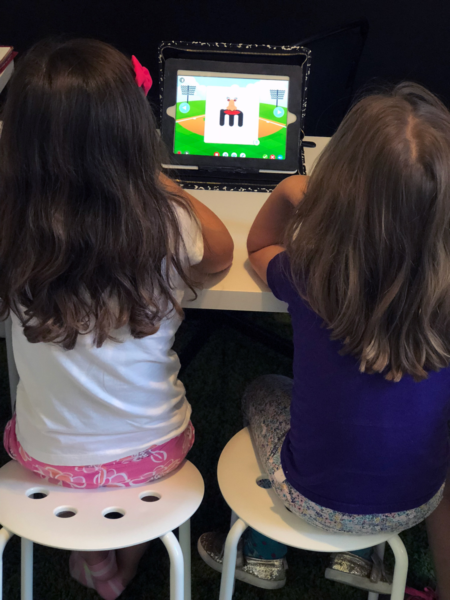 Two girls doing a speech activity on a tablet device.